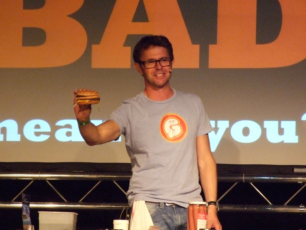"Stefan Gates at a live event with a Big Mac, discussing on the definition of ""bad"" food. He then went on to skin (and presumably cook) a pig's testicle. Yum. Image by Nelson Cunnington."